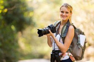 Jonge vrouw met fotocamera ter illustratie.